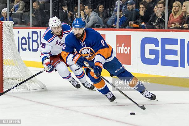 New York Rangers Left Winger Nicklas Jensen chases New York Islanders Defenseman Nick Leddy out from behind the Islanders net during the third period...