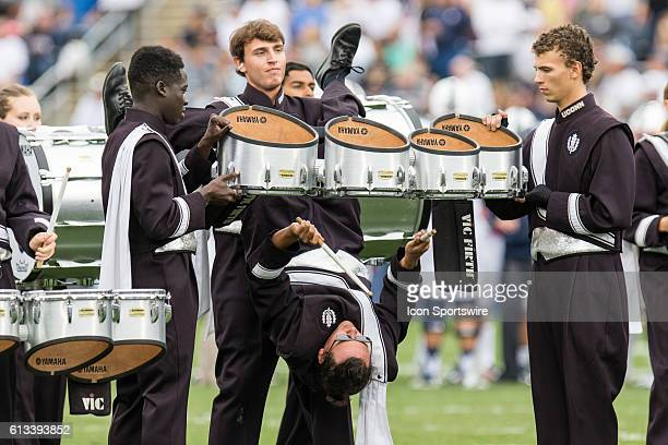 A member of the UConn drum line is suspended upside down while preforming between the third and fourth quarter of a NCAA football game between AAC...