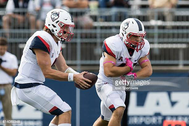 UConn Quarterback Bryant Shirreffs fakes a hand off to Michael Tarbutt during the first half of a NCAA football game between, AAC rivals, the...