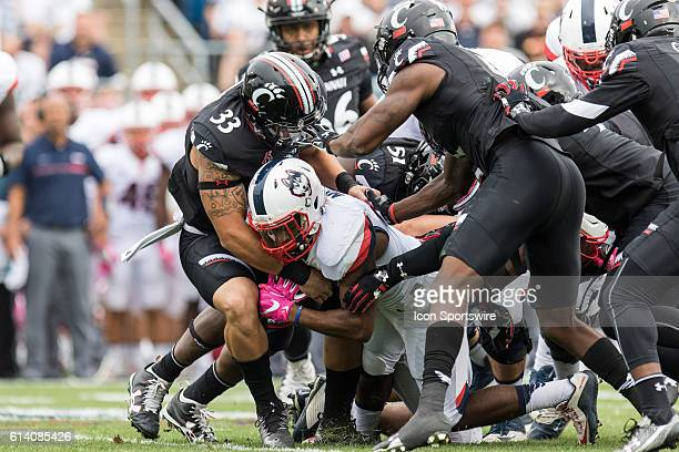 UConn Running Back Arkeel Newsome is brought down by a hoist of Cincinnati players during the first half of a NCAA football game between AAC rivals...