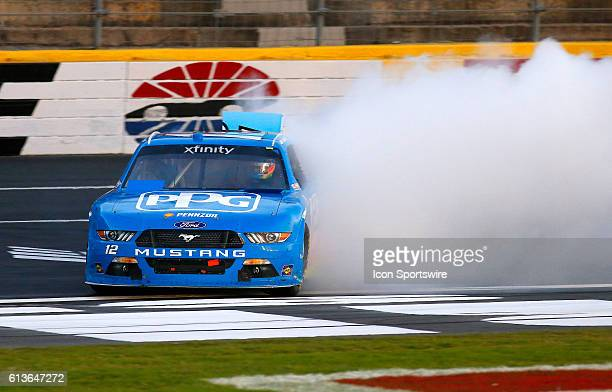 Joey Logano does a burnout after winning the Drive For The Cure 300 NASCAR Xfinity series racers the Charlotte Motor Speedway in Concord NC