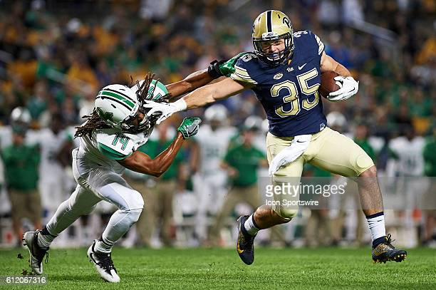 Pittsburgh Panthers fullback George Aston strong arms Marshall Thundering Herd safety Kendall Gant while carrying the ball for a touchdown in the...