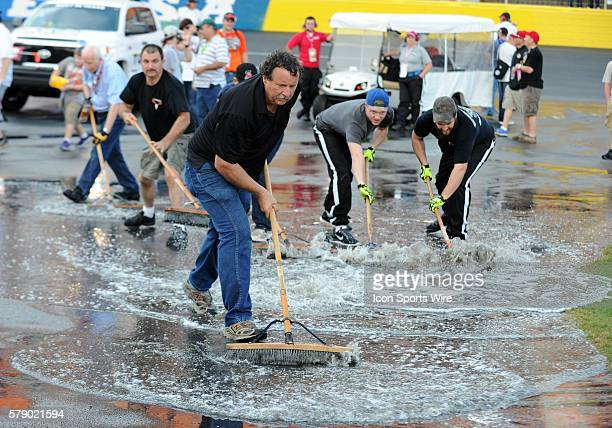 Workers of Charlotte Motor Speedway push water off the end of pit road hours before the Bank of America 500 at Charlotte Motor Speedway in ConcordNC