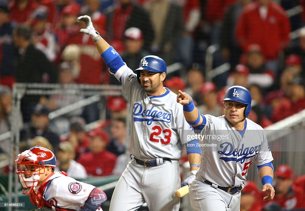 Los Angeles Dodgers catcher Carlos Ruiz (51) after scoring with first baseman Adrian Gonzalez (23) waves in left fielder Howie Kendrick (47) for two home runs in the seventh inning during game 5 of the NLDS at Nationals Park, in Washington D.C. The Los Angeles Dodgers defeated the Washington Nationals 4-3. to win the series.