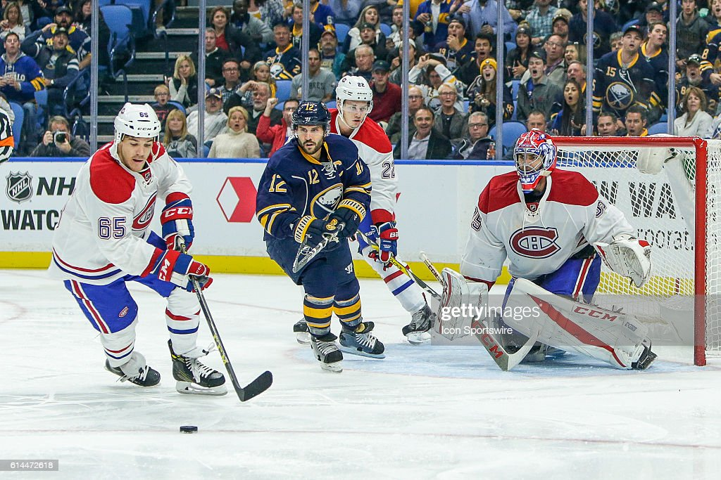Montreal Canadiens Winger Andrew Shaw (65) clears puck as Buffalo Sabres Right Wing Brian Gionta (12) Montreal Canadiens Defenseman Mikhail Sergachev (22) and Montreal Canadiens Goalie Al Montoya (35) look on during the Montreal Canadiens and Buffalo Sabres NHL game at Key Bank Center in Buffalo, NY