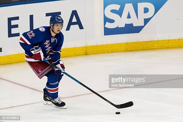 New York Rangers Defenseman Nick Holden looks to center the puck as he comes out from behind the net during the third period of opening night at...