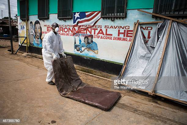 A nurse drags out a mattress coated with bodily fluids from inside the Island Clinic Ebola Treatment Unit on October 14 2014 in Monrovia Liberia