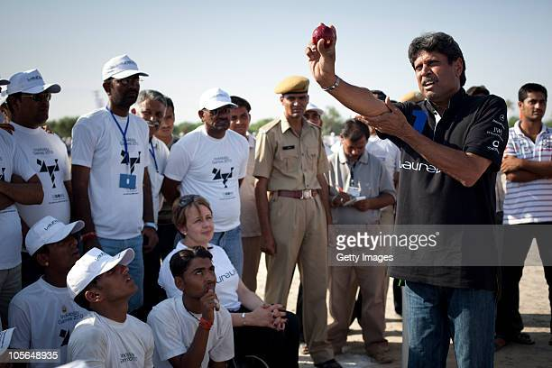 Laureus World Sports Academy member Kapil Dev gives a cricket lesson while Academy member TanniGrey Thompson looks on in the village of Sarecha as...
