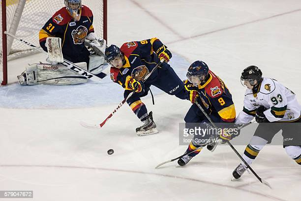 October 15, 2014. Cole Mayo of the Erie Otters clears the puck from in front of his goalie during a game between the London Knights and the Erie...
