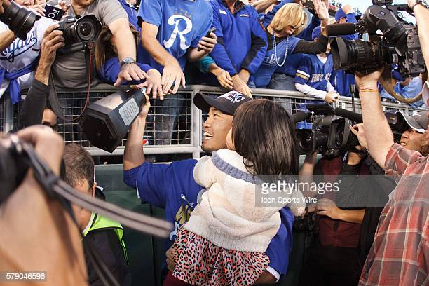 Kansas City Royals right fielder Nori Aoki allows fans to touch the American League Championship trophy after the Royals defeated the Baltimore...