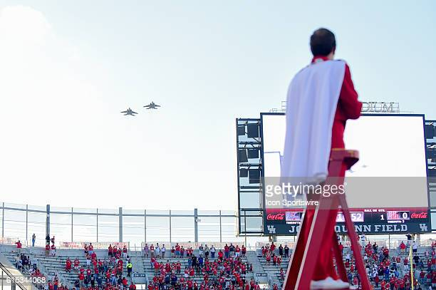 The crowd enjoys a flyby of two F-15C's during the National Anthem before the Tulsa Golden Hurricanes at Houston Cougars game at TDECU Stadium,...