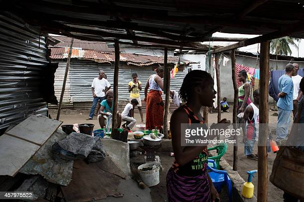 Residents gather outside their homes where Mary Nyanfort was suspected of dying of Ebola the day before on October 15 2014 in Monrovia Liberia Close...