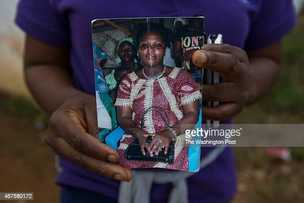 Prince Nyumahs sister holds a photo of their younger sister outside the Island Clinic Ebola treatment center where they have been searching for...