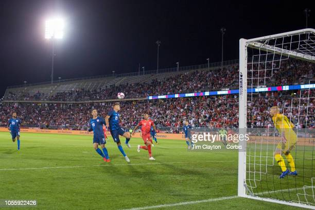 Aaron Long of the United States heads clear watched by Luis Advincula of Peru Ben Sweat of the United States and goalkeeper Brad Guzan of the United...