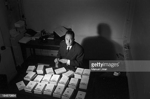 October 17 Albert Camus seated his books spread out before him on a table with the banner 'Nobel Prize'
