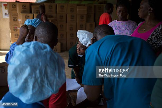 Nurses working at the Ebola holding center at the Ganta Hospital wait in line to receive rice in lieu if salary payment on October 17 2014 in Ganta...