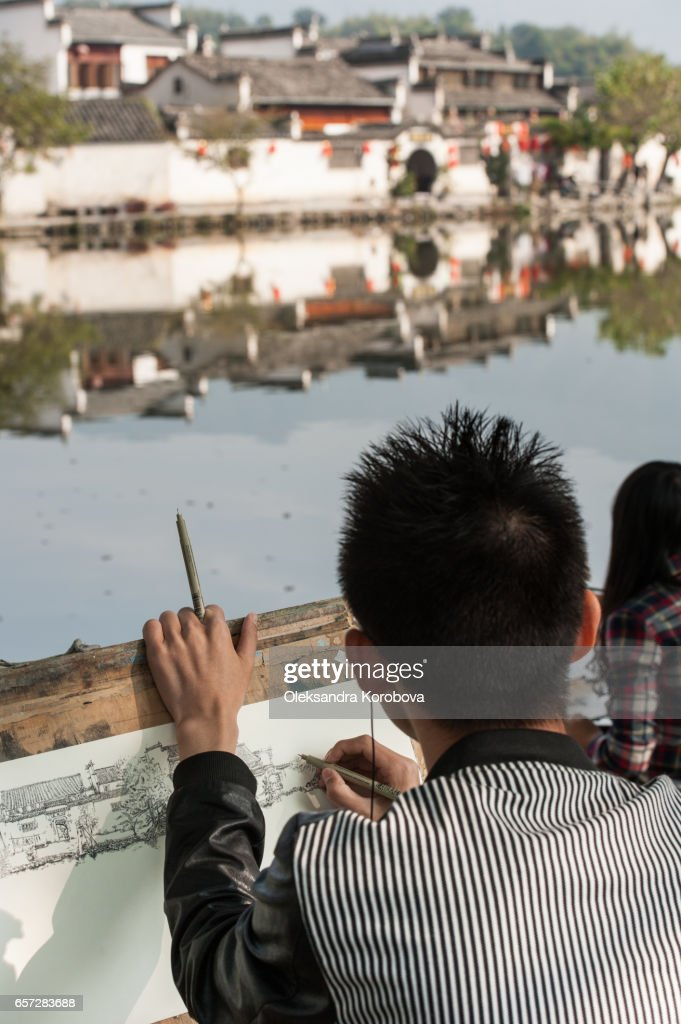 """October 18, 2014. Hongcun Village, China. Local students sketching the scenery near an ancient picturesque village that has long enjoyed the name """"a village in the Chinese painting"""" : Stock Photo"""