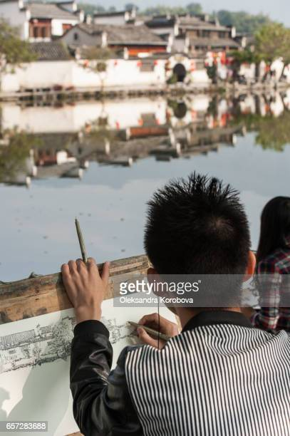 """october 18, 2014. hongcun village, china. local students sketching the scenery near an ancient picturesque village that has long enjoyed the name """"a village in the chinese painting"""" - istock stock pictures, royalty-free photos & images"""