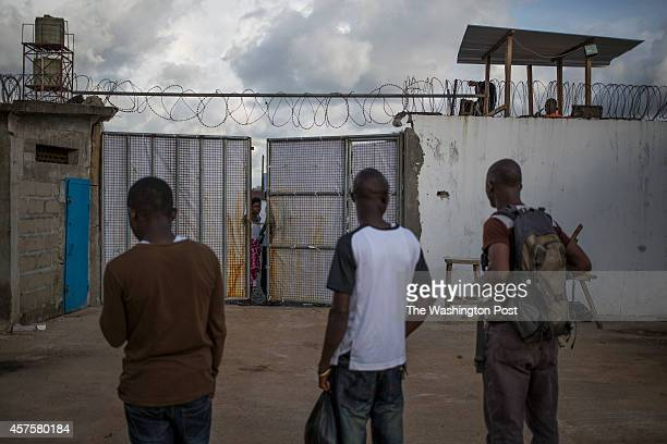 Family members and friends of Ebola patients wait in front of the gates of the Island Clinic Ebola treatment center hoping to find out information of...