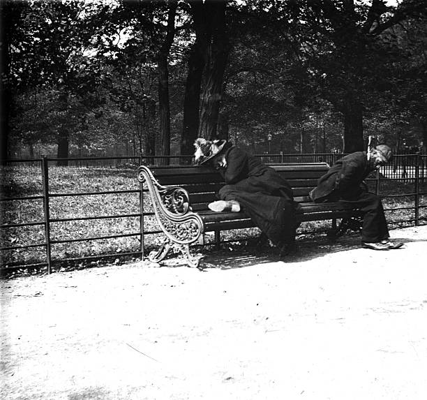 Vagrants asleep on a bench in St. James Park in London....