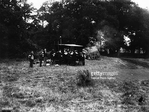 Workers who are constructing the Brooklands, Surrey racing circuit having a coffee break at a mobile canteen.