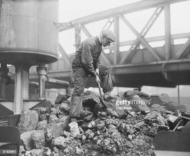 A man breaking up coal in a railway yard during the rail strike