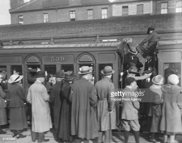 Passengers on the platform and crowded onto a train at Forest Gate Station during the railway strike