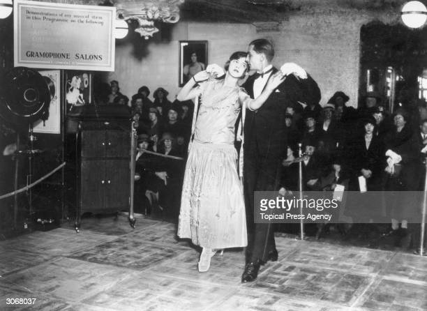 A couple of professional dancers accompany a gramophone demonstration in the music department of Harrods London