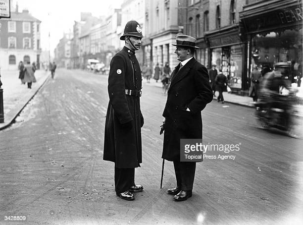 Parliamentary candidate Sidney Wells talking to a policeman during the Bedford election