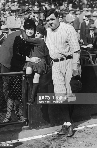 American baseball player for the Yankees Babe Ruth poses with his first wife Claire and their adopted daughter Dorothy on the sidelines before a game...