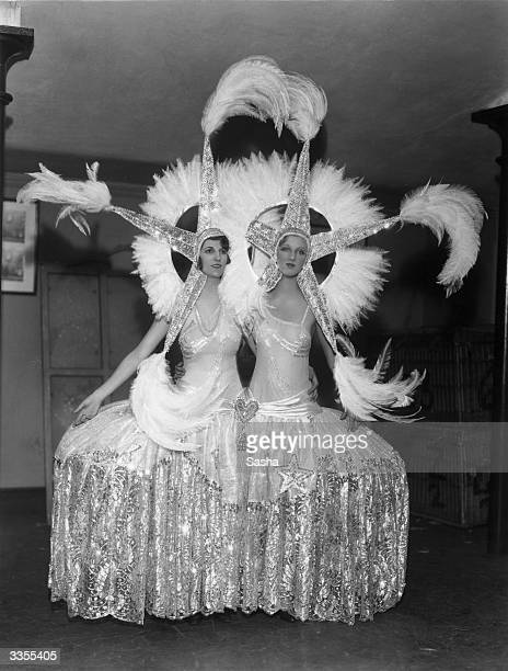 Two women in one extravagant costume involving star head dresses and feather halos The dress is joined into one skirt at the hip and was made for...