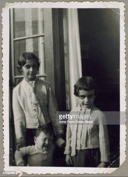 EXCLUSIVE Anne Frank her sister Margot Frank and an unidentified crying child standing on a balcony From Anne Frank's photo album