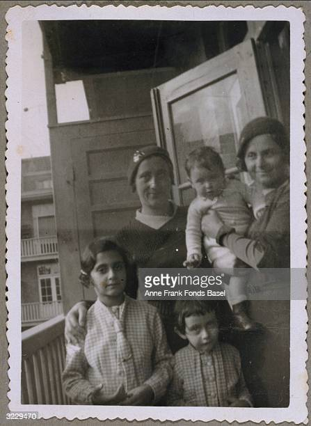 EXCLUSIVE Anne Frank her sister Margot Frank their mother Edith FrankHollander and a woman holding a child standing on a balcony From Anne Frank's...