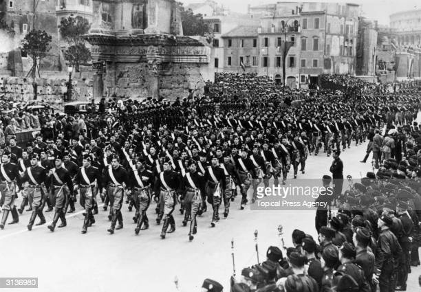 Young fascist in their black shirts marching past Mussolini