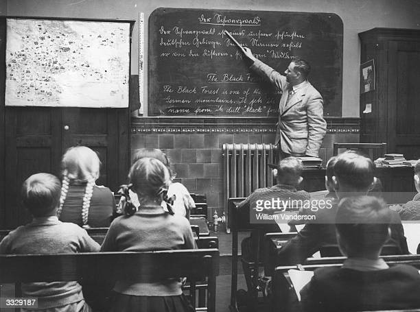 A teacher at St Mary's School Cleveland Street London which caters for English and German children teaches a lesson in English and German The...