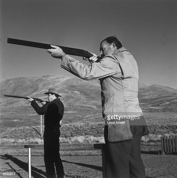 American writer Ernest Hemingway and his friend, Gene Van Guilder, take aim with shotguns during the pheasant season, Idaho, October, 1939.