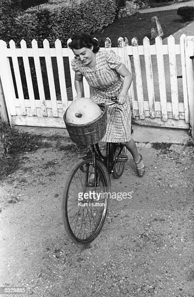 A woman balances a pumpkin in her bicycle basket on the way to a harvest festival during the Second World War Original Publication Picture Post 887...