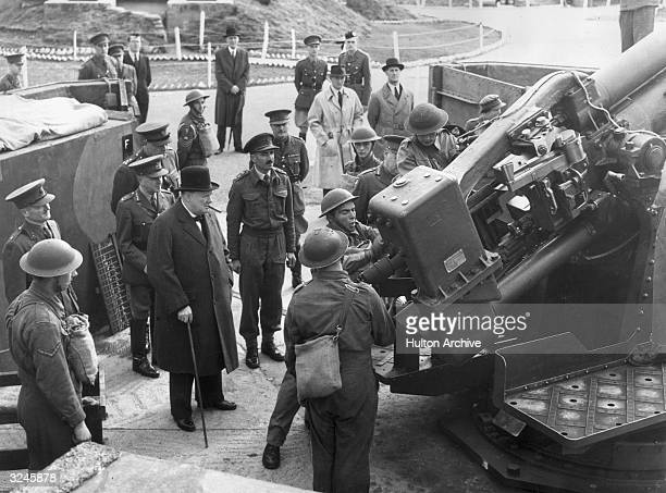 British Prime Minister Winston Churchill observes British soldiers operating a static 37in antiaircraft gun during the Blitz London England
