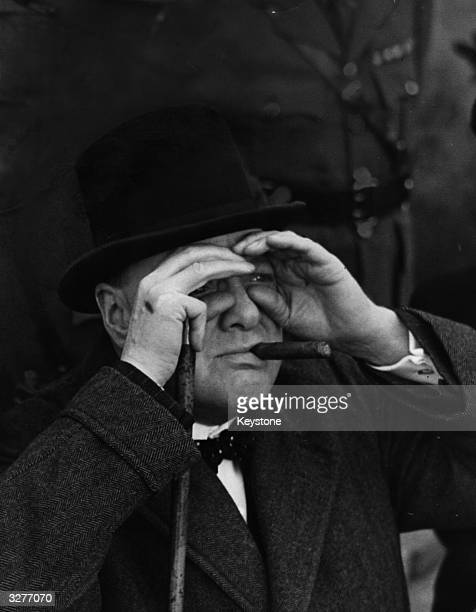 British Prime Minister Winston Churchill shields his eyes during a visit to an antiaircraft site in the London area