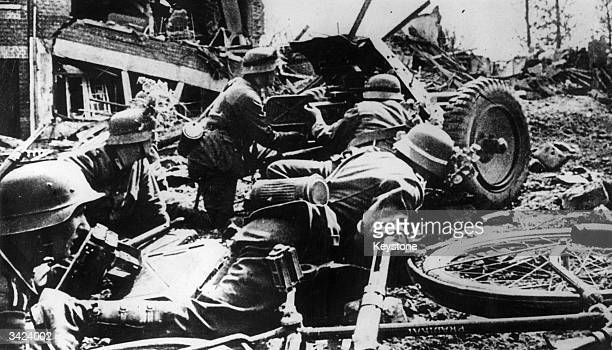 In a devastated section on the Russian front German troops fire an antitank gun at retreating Russians