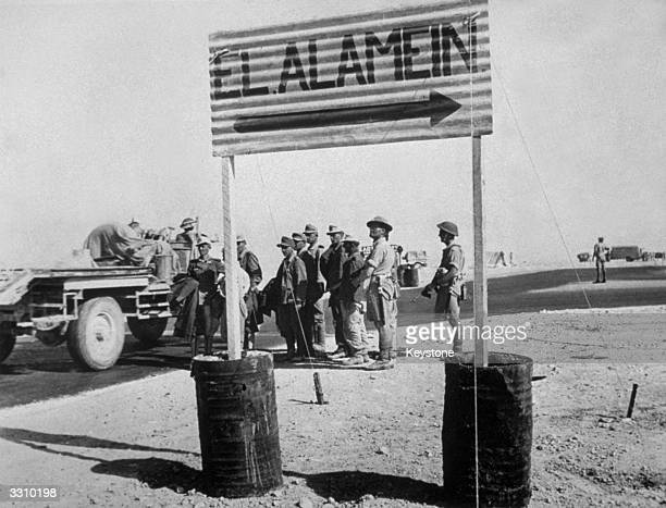 German prisoners from the Afrika Korps passing a sign to El Alamein in the north African desert Egypt after the Battle of El Alamein