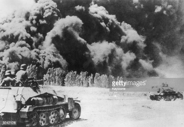German soldiers in armoured halftrack vehicles pass an oil field set on fire by retreating Russians
