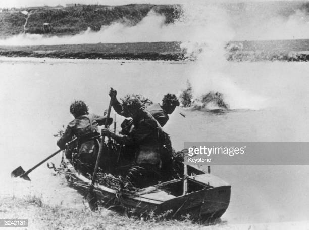 Using shovels to paddle their boat a group of Romanian soldiers attempt to cross a river in the Caucasus under Russian artillery fire