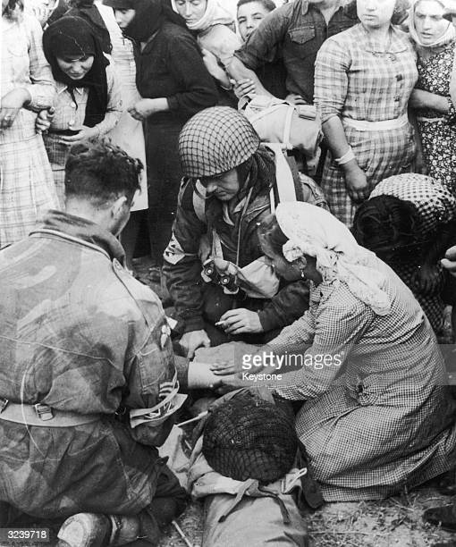 Greek woman helps to dress the injured foot of a British paratrooper during the allied liberation of Greece.
