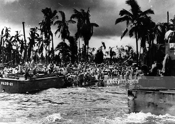 The constant stream of supplies keep coming and the American troops stand knee deep in the water passing them to the shore in the Philippines