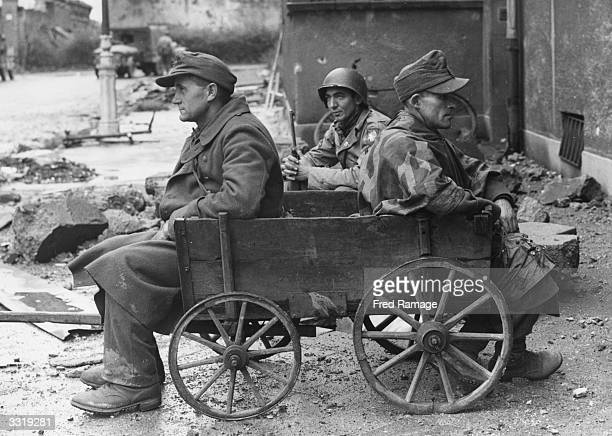 Two German prisoners of war in a debris strewn street in Aachen are resting on a barrow whilst waiting for transport to a POW camp An American...