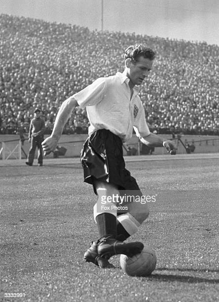 Tom Finney, right winger for Preston North End Football Club, on the ball whilst playing for England.