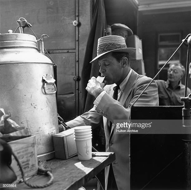 American actor William Holden sips water from a cup on the set of director Billy Wilder's film 'Sabrina' Holden wears a lightcolored blazer and a...