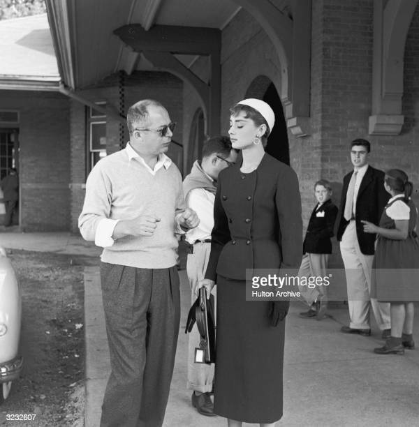 Austrian-born film director Billy Wilder talks with Belgian-born actor Audrey Hepburn as they stand in a train station on the set of the film,...