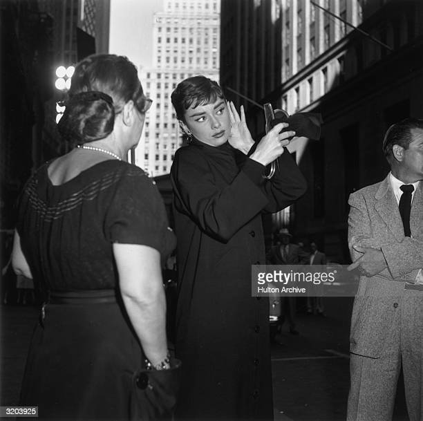 Belgianborn actor Audrey Hepburn fixes her hair while looking into a handheld mirror in front of skyscrapers on the set of director Billy Wilder's...